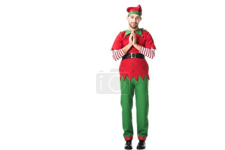 Photo for Man in christmas elf costume holding palms together as please gesture and having hopeful expression isolated on white - Royalty Free Image