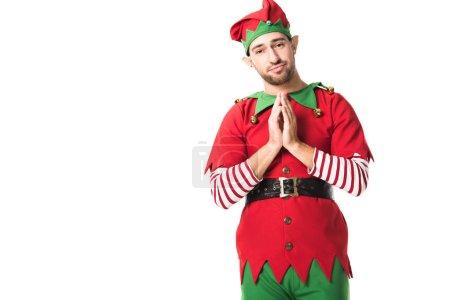 Foto de Hombre en traje de elfo de Navidad con las palmas juntas como por favor gesto y tener expresión esperanzadora aislada en blanco - Imagen libre de derechos