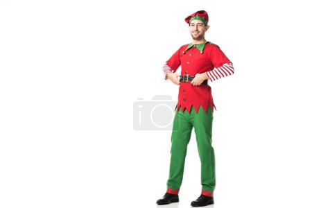 smiling man in christmas elf costume looking at camera with hands on hips isolated on white