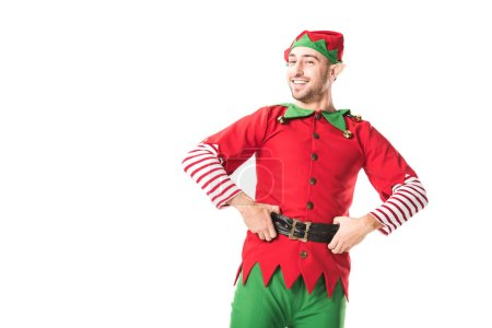cheerful man in christmas elf costume looking at camera with hands on hips isolated on white