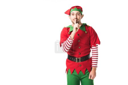man in christmas elf costume showing hush silence sign and looking at camera isolated on white