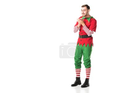 excited smiling man in christmas elf costume looking at camera and rubbing hands in anticipation isolated on white