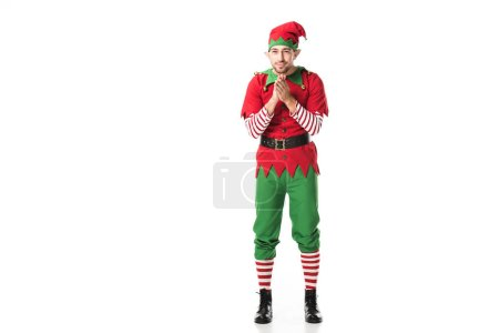 excited man in christmas elf costume looking at camera and rubbing hands in anticipation isolated on white