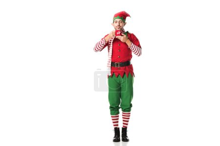 man in christmas elf costume with eyes closed holding cup of tea and inhaling aroma isolated on white