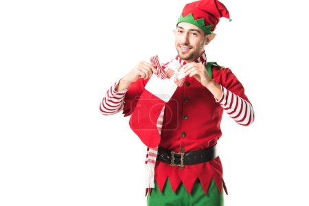 smiling man in christmas elf costume putting present in red christmas stocking and looking at camera isolated on white