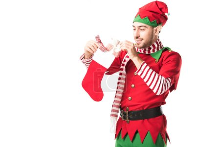 man in christmas elf costume putting present in red christmas stocking isolated on white