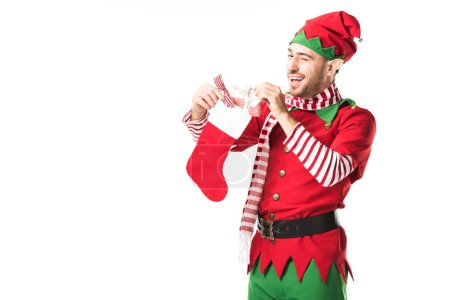 man in christmas elf costume winging and putting present in red christmas stocking isolated on white