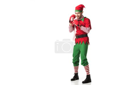 man in christmas elf costume wearing red boxing gloves and ready for fight isolated on white