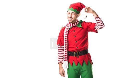 smiling man in christmas elf costume holding bauble and looking at camera isolated on white