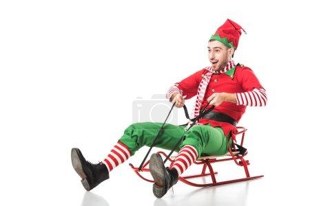 Photo pour Excité homme en costume d'elfe de Noël équitation traîneau isolé sur fond blanc - image libre de droit