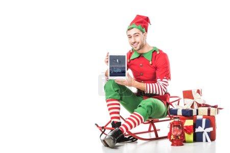 Foto de Hombre en traje de elfo de Navidad sentado en trineo y de sostener la tablet con la app de tumblr en pantalla aislada en blanco - Imagen libre de derechos