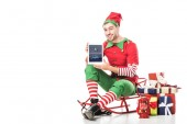 man in christmas elf costume sitting on sleigh and holding tablet with tumblr app on screen isolated on white