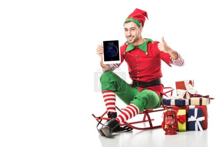 Photo for Man in christmas elf costume sitting on sleigh and holding tablet with apple home screen isolated on white - Royalty Free Image