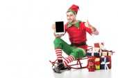 man in christmas elf costume sitting on sleigh and holding tablet with blank screen isolated on white