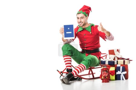 man in christmas elf costume sitting on sleigh and holding tablet with facebook app on screen isolated on white
