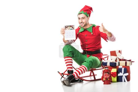 man in christmas elf costume sitting on sleigh, showing thumbs up and holding tablet with forsquare app isolated on white