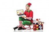 man in christmas elf costume sitting on sleigh and holding laptop with aliexpress website on screen isolated on white
