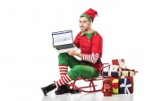 man in christmas elf costume sitting on sleigh and holding laptop with facebook website on screen isolated on white