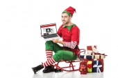 man in christmas elf costume sitting on sleigh and holding laptop with bbc news website on screen isolated on white