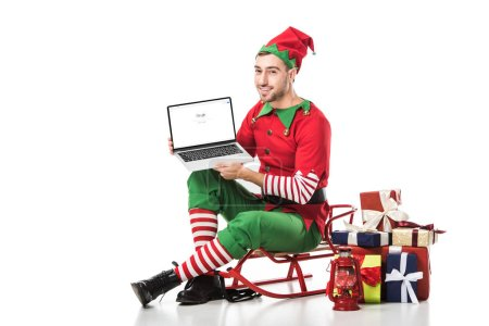 Photo for Man in christmas elf costume sitting on sleigh and holding laptop with google website on screen isolated on white - Royalty Free Image