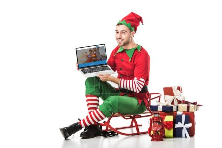 Photo for Man in christmas elf costume sitting on sleigh and holding laptop with couchsurfing website on screen isolated on white - Royalty Free Image