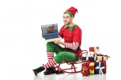 man in christmas elf costume sitting on sleigh and holding laptop with couchsurfing website on screen isolated on white
