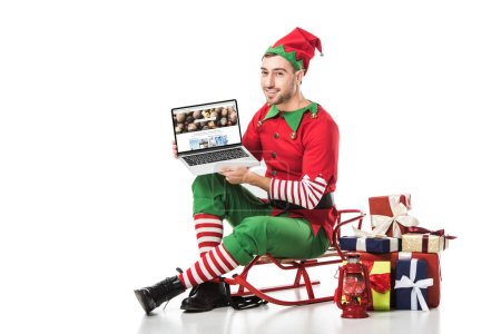 Photo for Man in christmas elf costume sitting on sleigh and holding laptop with depositphotos website on screen isolated on white - Royalty Free Image