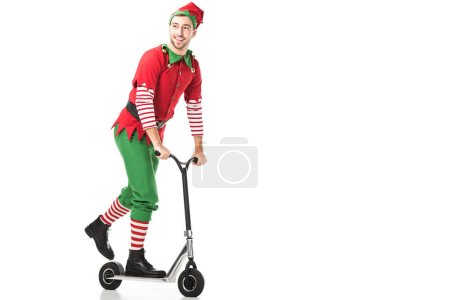 Photo for Cheerful man in christmas elf costume riding push-cycle and looking away isolated on white - Royalty Free Image