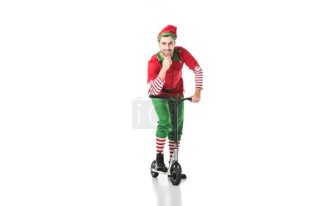 happy man in christmas elf costume touching chin and riding push-cycle isolated on white