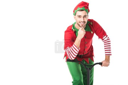 smiling man in christmas elf costume looking at camera, touching chin and riding push-cycle isolated on white
