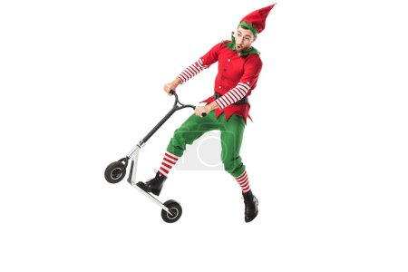 excited man in christmas elf costume jumping in air on push-cycle isolated on white