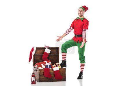 smiling man in christmas elf costume standing near wooden chest full of presents with outstretched hands isolated on white