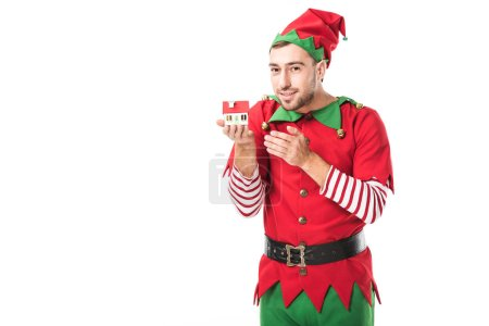 man in christmas elf costume holding house model isolated on white, real estate sale and insurance concept