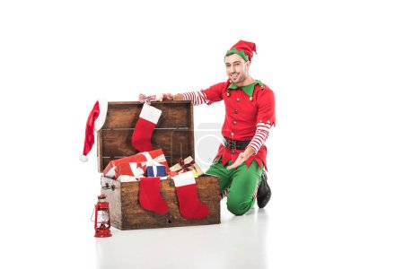 man in christmas elf costume sitting on wooden chest with christmas stockings and presents isolated on white