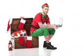 smiling man in christmas elf costume sitting on wooden box and using laptop isolated on white