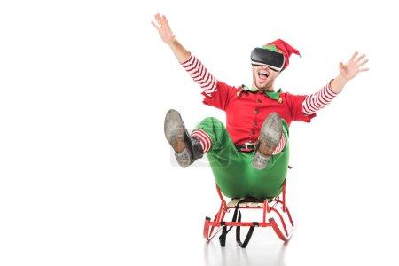 Foto de Hombre excitado en traje de elfo de Navidad trineo del montar a caballo y el uso de casco de realidad virtual aislado en blanco - Imagen libre de derechos