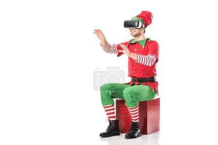 Foto de Hombre en traje de elfo de Navidad sentado en la caja y el uso de casco de realidad virtual aislado en blanco - Imagen libre de derechos