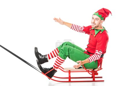 excited happy man in christmas elf costume riding sleigh and looking at camera isolated on white