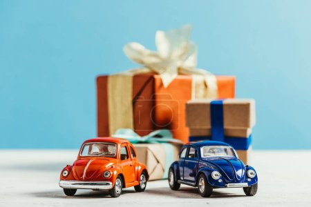 close-up shot of toy cars with christmas gift boxes on blue background