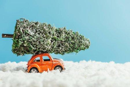 Foto de Vista lateral del vehículo de juguete con árbol de Navidad en miniatura en la azotea del montar a caballo por la nieve de algodón sobre fondo azul - Imagen libre de derechos