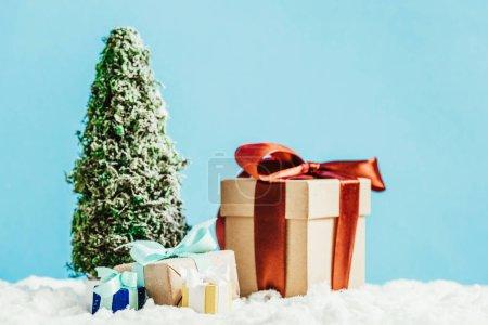 Foto de Close-up foto de regalos de Navidad y árbol de Navidad miniatura sobre nieve en fondo azul - Imagen libre de derechos