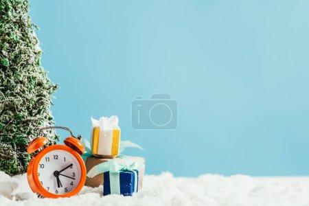 Foto de Close-up foto de regalos de Navidad con despertador y árbol de Navidad miniatura sobre nieve en fondo azul - Imagen libre de derechos