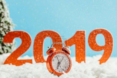 Foto de Números rojo 2019 con despertador de pie sobre la nieve en el fondo azul, año nuevo concepto - Imagen libre de derechos