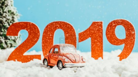 big red 2019 numbers with toy car standing on snow on blue background, new year concept