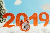 big red 2019 numbers with vintage alarm clock standing on snow on blue background, new year concept