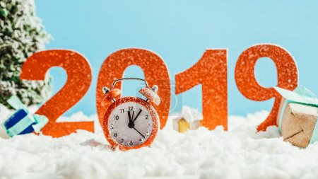 big red 2019 numbers with vintage alarm clock and gifts on snow on blue background, new year concept