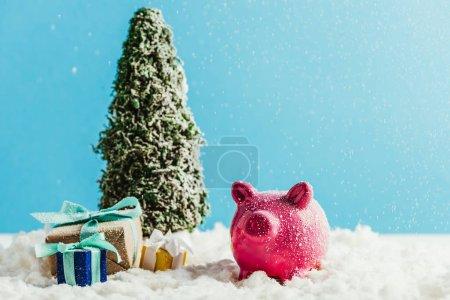 Photo pour Arbre de Noël miniature avec des cadeaux et commandes tirelire sur neige sur fond bleu - image libre de droit