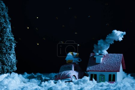 close-up shot of toy car with christmas gift and house covered with snow in night