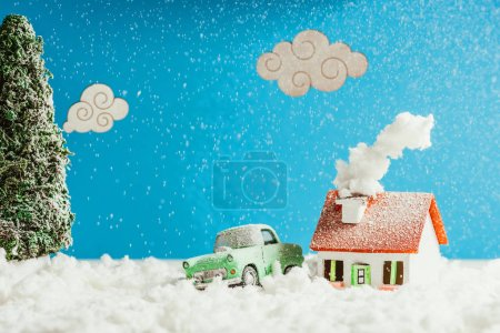close-up shot of toy car and house covered with snow, christmas concept