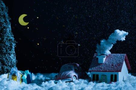 Foto de Primer tiro de coche de juguete con regalos de Navidad y la casa cubierto de nieve en la noche - Imagen libre de derechos